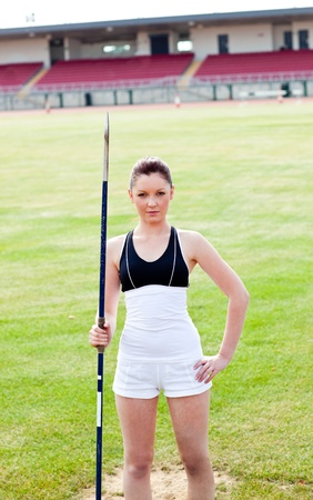 Confident athletic woman ready to throw a javelin standing in a stadium Stock Photo - 10243983