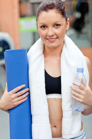 Sporty woman holding a bottle of water and an exercise mat looking at the camera photo