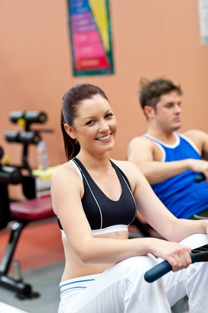 musculation: Beautiful woman using a rower with her boyfriend in a fitness center