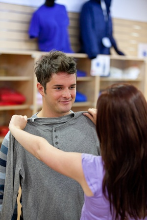 Handsome man with his girlfriend trying on clothes in a shopping centre photo