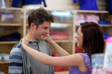 Cheerful couple choosing clothes standing in the men department photo