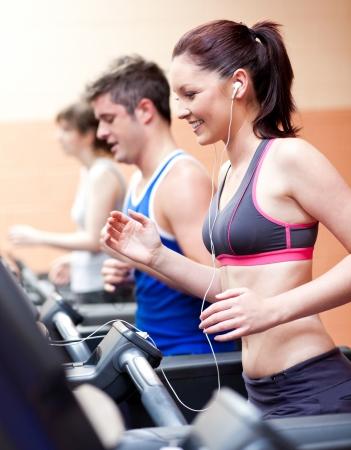 actief luisteren: Mooie vrouwelijke atleet staat op een draaiende machine te luisteren naar de muziek Stockfoto
