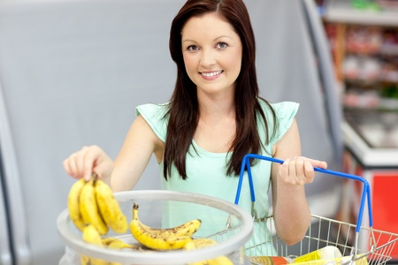 Healthy woman with shopping-basket buying bananas in a grocery store Stock Photo - 10244105