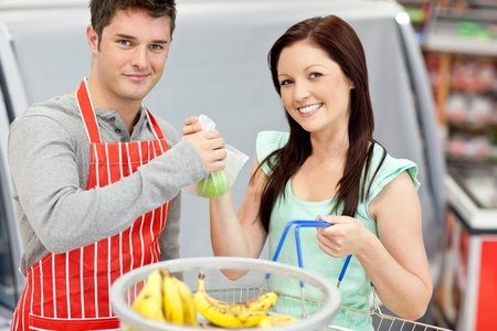 Salesman in a grocery store giving apples to his smiling female customer Stock Photo - 10244290