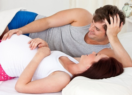 Cute man touching the belly of his pregnant wife lying on the bed at home photo