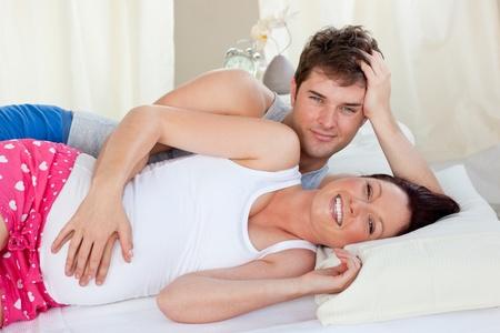 homme enceinte: Heureuses futurs parents allong� sur le lit pendant la matin�e sourire � la cam�ra