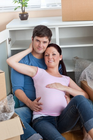 Happy couple in their new home sitting on the floor among cardboard boxes photo
