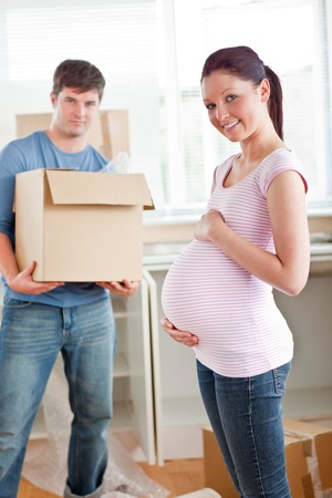 Adorable pregnant woman with husband holding cardboard in the kitchen  photo