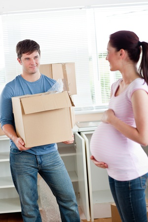 Smiling man with cardboard looking at his pregnant wife standing in their new kitchen photo