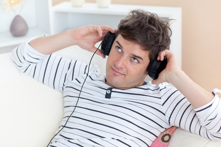 Thoughful man listening music looking the top sitting in the sofa Stock Photo - 10244115