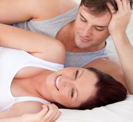 Close-up of an affectionate man looking at his pregnant wife lying on the bed photo