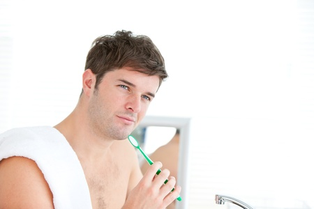 Smart young male brushing his tooth with towel on his shoulder photo