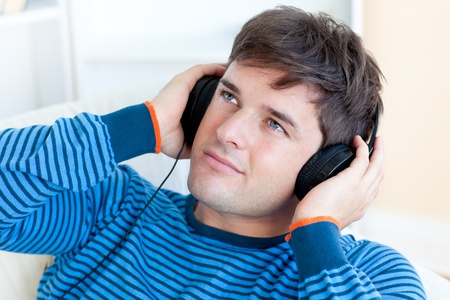 Attractive young man listening music sitting in the living-room photo