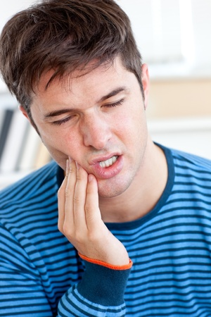 toothache: Portrait of a man having a raging toothache sitting in the living-room Stock Photo