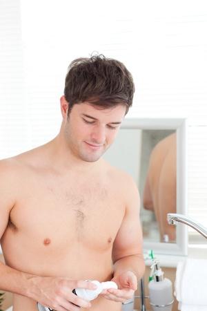 Happy man putting shaving-foam standing in his bathroom photo
