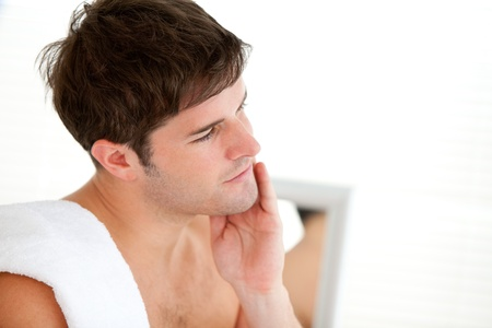 shaving blade: Handsome man looking his face in the mirror after shaving Stock Photo