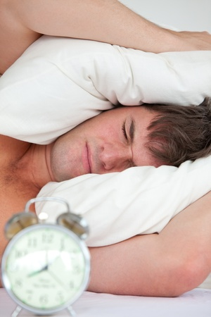 Young male adult stressed by his alarm clock with his head under the pillow photo