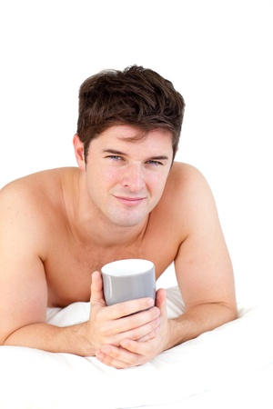 Young male adult holding a cup of tea lying on his bed photo