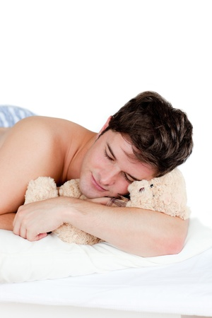 Young man in pajamas sleeping with a teddy bear lying on his bed photo