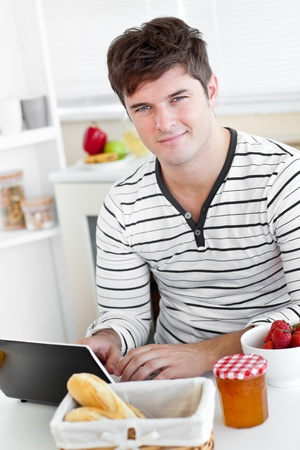 Young man using his laptop during his breakfast sitting in the kitchen photo