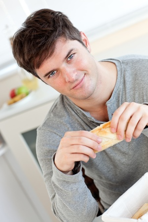 Attractive young man eating bread sitting in his kitchen photo