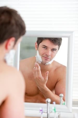 mirar espejo: Joven poniendo algunos permanente en el ba�o de espuma de afeitar