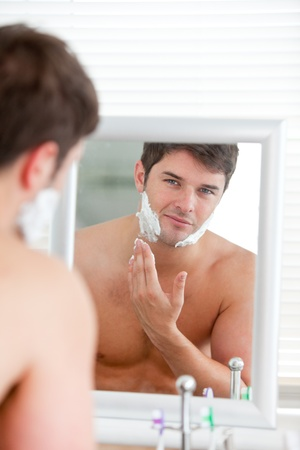 shaving blade: Young man putting some shaving foam standing in the bathroom Stock Photo