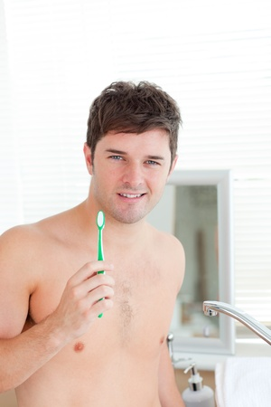Smart young man holding his toothbrush in the bathroom in the morning photo