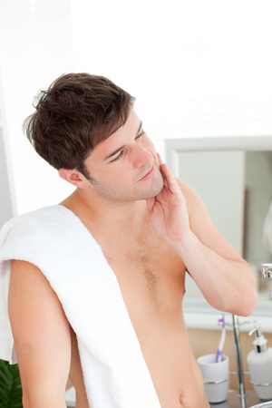 white towel: Smiling man touching his face after shaving Stock Photo