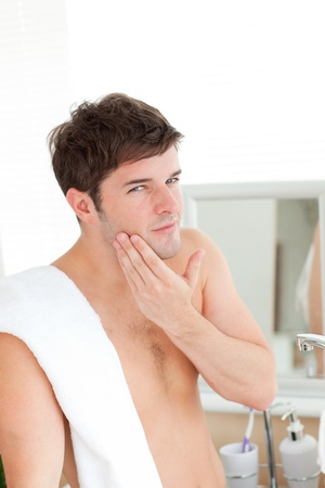 razor blade: Young man putting aftershave in the bathroom
