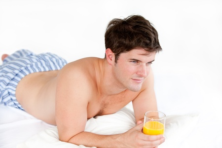 Handsome boy in pajamas holding a glass of orange juice lying on his bed photo