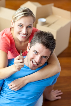 unpacking: Portrait of a joyful couple in their new house with woman showing the key