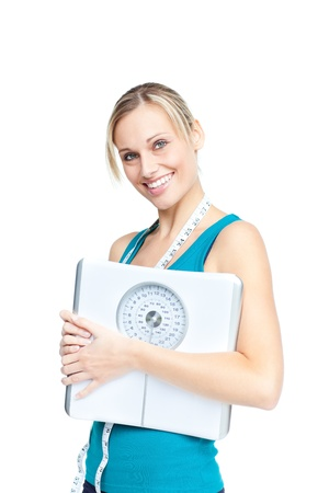 Bright woman holding a scales and a measuring tape smiling at the camera photo