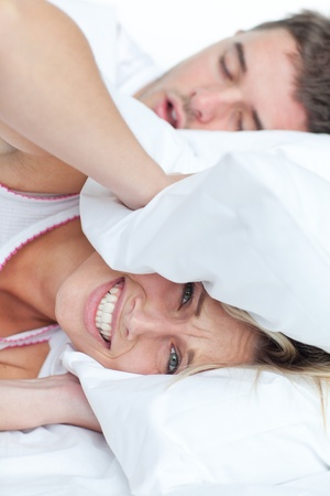 snore: Stressed woman lying on the bed with her boyfriend snoring
