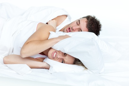 disturbed: Upset woman in bed with her boyfriend snoring  Stock Photo