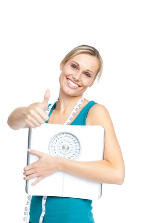 Attractive young woman holding a weight scale looking at the camera photo