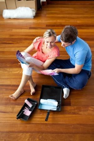 primeramente: pareja atractiva se sienta en el piso de colores de picking Foto de archivo