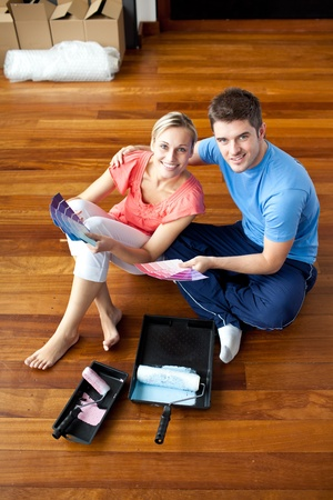 first time buyer: Beautiful couple sits on the floor picking colors Stock Photo