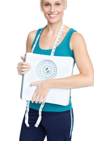 Smiling young woman holding a weight scale looking at the camera photo