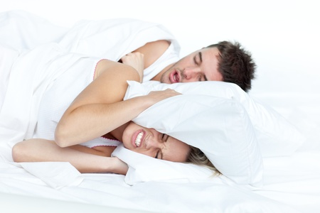 snore: Couple in bed while the woman is trying to sleep