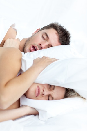 snore: Young couple lying in bed  Stock Photo