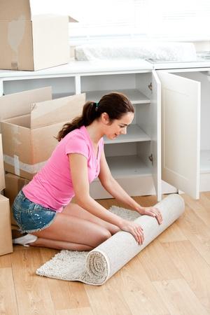 Joyful woman rolling a carpet out photo