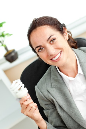Bright hispanic businesswoman holding a light bulb sitting at her desk photo