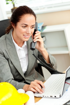 Hispanic female architect using her laptop while talking on phone Stock Photo - 10243992