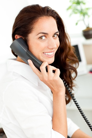 Positive hispanic businesswoman talking on phone photo