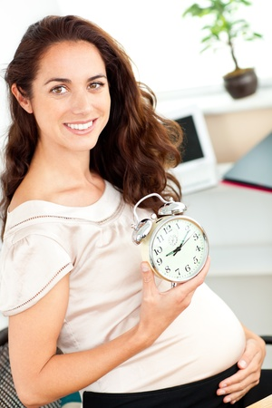 Radiant pregnant businesswoman holding an alarm clock and sitting at her desk photo