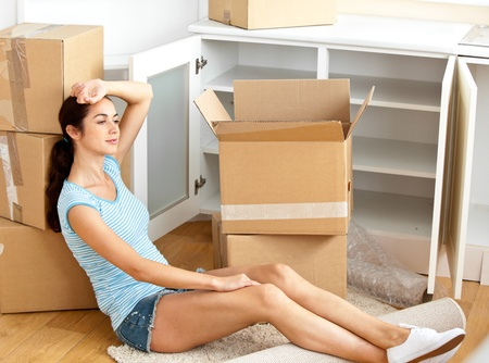 packing: Exhausted hispanic young woman sitting on the floor after unpacking boxes