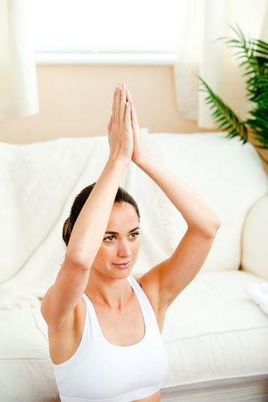 Bright hispanic woman meditating in her living-room photo