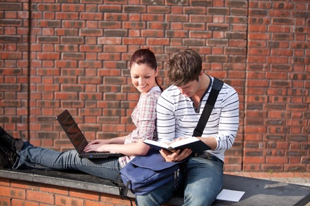 Two students working together with book and laptop outside photo