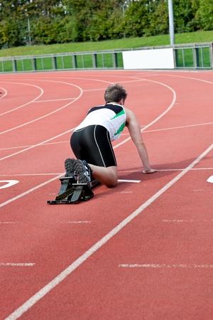 Athletic man waiting in starting block photo